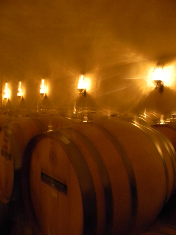 Low, flickering lights playing off the barrels in a wine cellar.